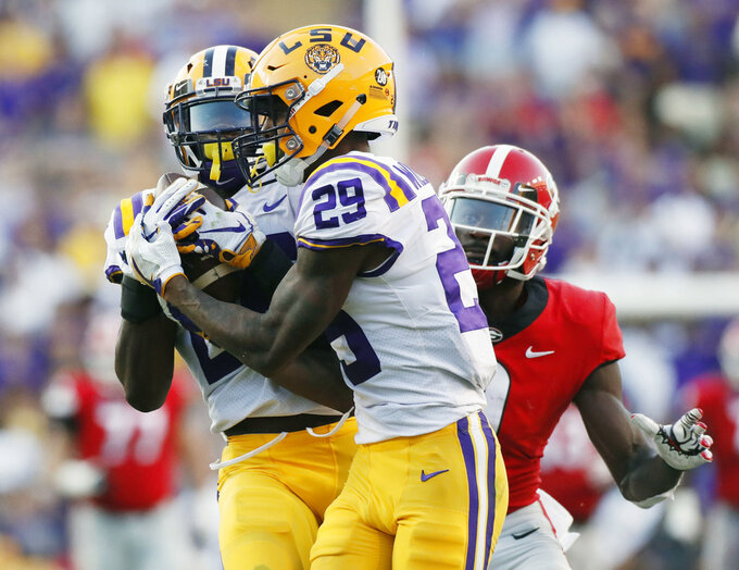 LSU safety John Battle (26), with assistance from cornerback Greedy Williams (29), intercepts a pass from Georgia quarterback Jake Fromm intended for wide receiver Jeremiah Holloman, rear, during the fourth quarter of an NCAA college football game Saturday, Oct. 13, 2018, in Baton Rouge, La. (Bob Andres/Atlanta Journal Constitution via AP)