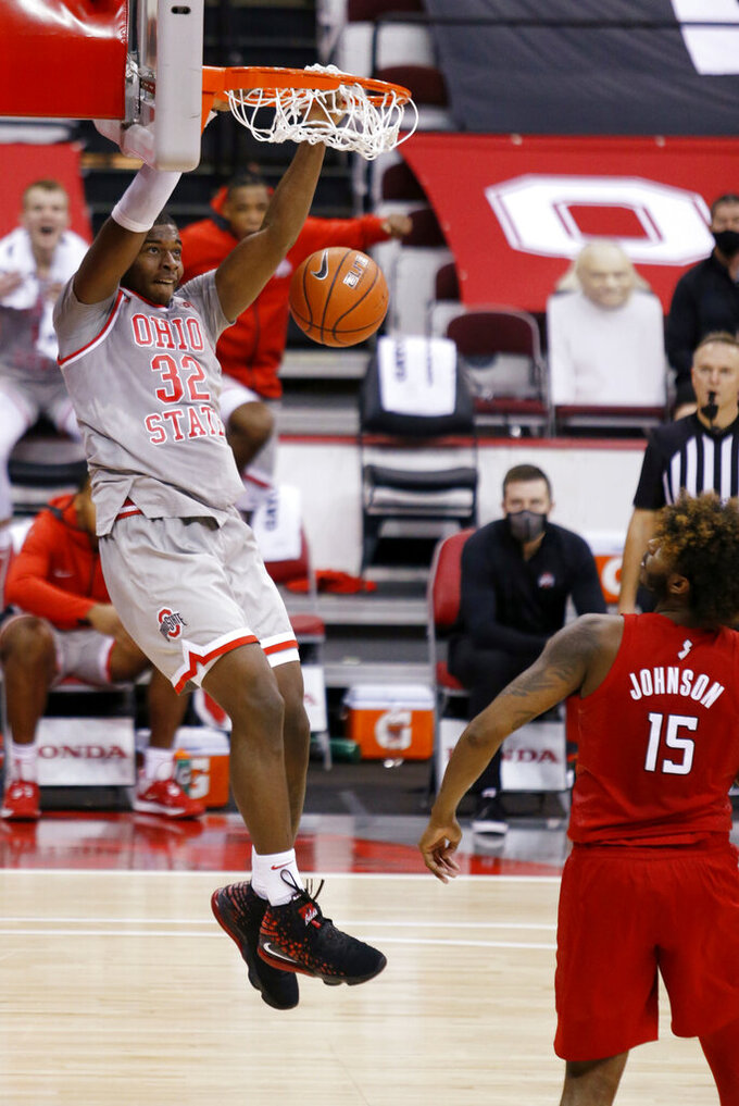 Ohio State forward E.J. Liddell, left, dunks next to Rutgers center Myles Johnson during the second half of an NCAA college basketball game in Columbus, Ohio, Wednesday, Dec. 23, 2020. (AP Photo/Paul Vernon)