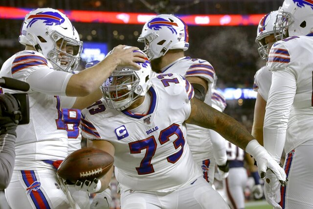 Buffalo Bills quarterback Josh Allen, left, celebrates his touchdown pass to offensive tackle Dion Dawkins, center, in the first half of an NFL football game against the New England Patriots, Saturday, Dec. 21, 2019, in Foxborough, Mass. (AP Photo/Steven Senne)