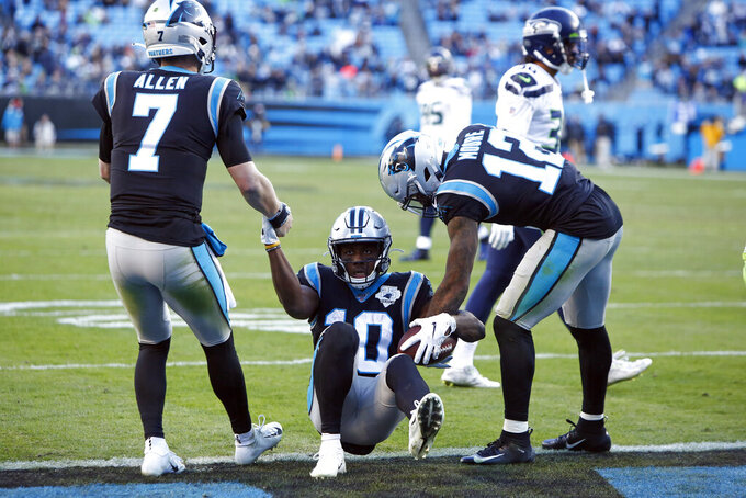Carolina Panthers quarterback Kyle Allen (7) and wide receiver D.J. Moore (12) assist wide receiver Curtis Samuel (10) following Samuel's touchdown against the Seattle Seahawks during the second half of an NFL football game in Charlotte, N.C., Sunday, Dec. 15, 2019. (AP Photo/Brian Blanco)