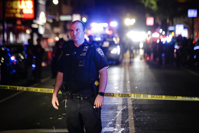 A New York City police officer stands on a street early Thursday, June 4, 2020, in the Brooklyn borough of New York. The police department says an officer has been shot in Brooklyn. The shooting happened late Wednesday, nearly four hours after an 8 p.m. curfew went into effect intended to quell unrest over the death of George Floyd in Minnesota. Details on the shooting, including the officer's condition, weren't immediately available. (AP Photo/Frank Franklin II)
