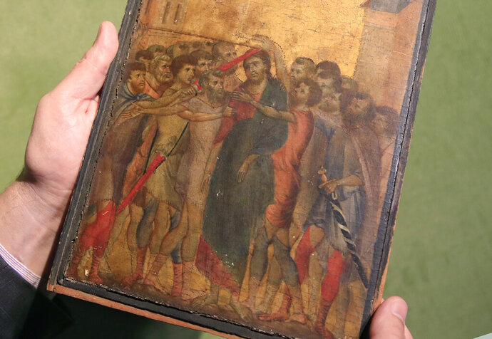 FILE - In this Tuesday, Sept. 24, 2019 file photo, art expert Stephane Pinta points to a 13th-century painting by Italian master Cimabue in Paris, Tuesday, Sept. 24, 2019. A masterpiece attributed to the 13th-century Italian painter Cimabue that was discovered in an elderly French woman's kitchen is expected to sell for millions at auction. Stephane Pinta, a painting specialist with the Turquin gallery in Paris, said an auctioneer spotted the painting while inspecting the woman's house in Compiegne in northern France and suggested she bring it to experts for an evaluation. (AP Photo/Michel Euler, File )