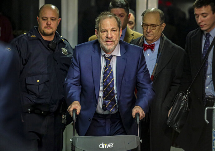 Harvey Weinstein, second from left, leaves Manhattan's Criminal Court after prosecutors completed their closing argument in his rape trial, Friday, Feb. 14, 2020, in New York. (AP Photo/Bebeto Matthews)