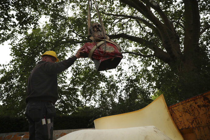 A workman guides a bust of Belgium's King Leopold II as it is set into the back of a truck after being hoisted off of its plinth and removed from a park in Ghent, Belgium on Tuesday, June 30, 2020. Protests sweeping the world after George Floyd's death in the U.S. have added fuel to a movement to confront Europe's role in the slave trade and its colonial past. Leopold II is increasingly seen as a stain on the nation where he reigned from 1865 to 1909 with some demonstrators calling for his removal from public view. (AP Photo/Francisco Seco)
