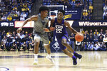 FILE - TCU guard RJ Nembhard (22) is defended by West Virginia guard Miles McBride during the first half of an NCAA college basketball game in Morgantown, W.Va., in this Tuesday, Jan. 14, 2020 file photo. TCU coach Jamie Dixon isn't expecting center Kevin Samuel and guard RJ Nembhard to play more minutes this season. The team's only returning starters just need to be more efficient when on the court. (AP Photo/Kathleen Batten, File)