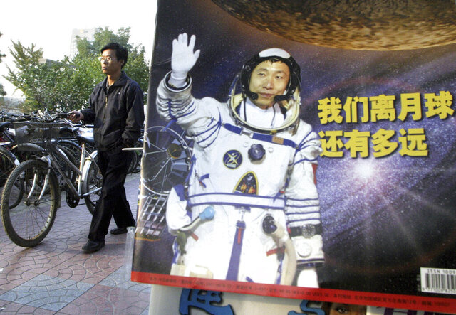 In this photo taken Thursday, Oct 23, 2003, a man pushes his bicycle past the cover of a magazine showing China's first man in space, Yang Liwei and the Chinese characters for