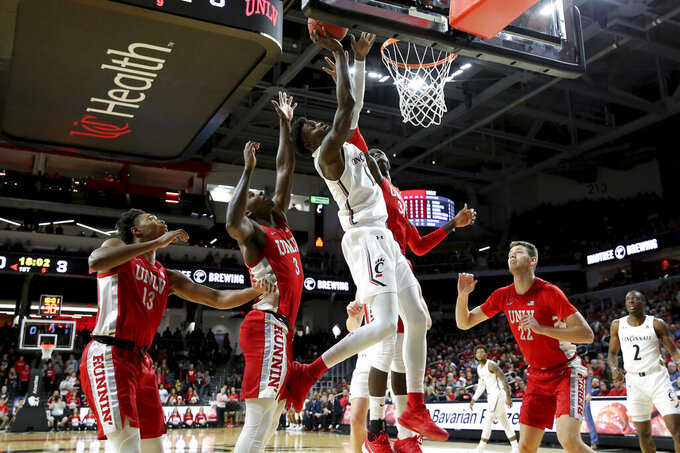 Cincinnati forward Trevon Scott (13) pulls down a rebound next to UNLV forward Cheikh Mbacke Diong (34) in the first half of an NCAA college basketball game Saturday, Nov. 30, 2019, in Cincinnati. (Kareem Elgazzar/The Cincinnati Enquirer via AP)