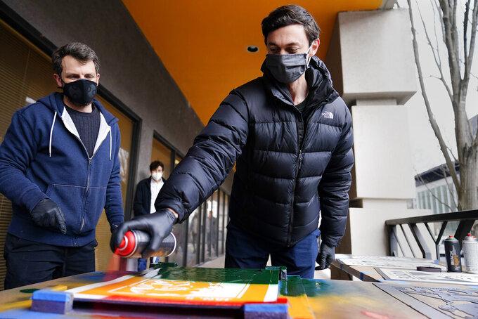 U.S. Senator-elect Jon Ossoff, D-Ga., right, spray paints a campaign poster with Brandon Litman, 39, left, of Brooklyn, N.Y. after Georgia's Senate runoff race on Saturday, Jan. 9, 2021, in Atlanta. (AP Photo/Brynn Anderson)