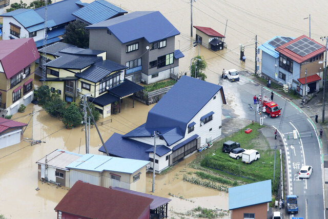 A residential area is flooded following a heavy rain in Okura village, Yamagata prefecture, northern Japan Wednesday, July 29, 2020. (Kyodo News via AP)