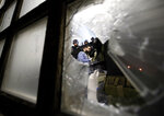 Serbian police officers escort a protester against the autocratic rule of Serbian President Aleksandar Vucic into state-run TV headquarters in Belgrade, Serbia, Saturday, March 16, 2019. Riot police arrived at the scene in downtown Belgrade and were trying to evict dozens who had entered the downtown building. (AP Photo/Darko Vojinovic)