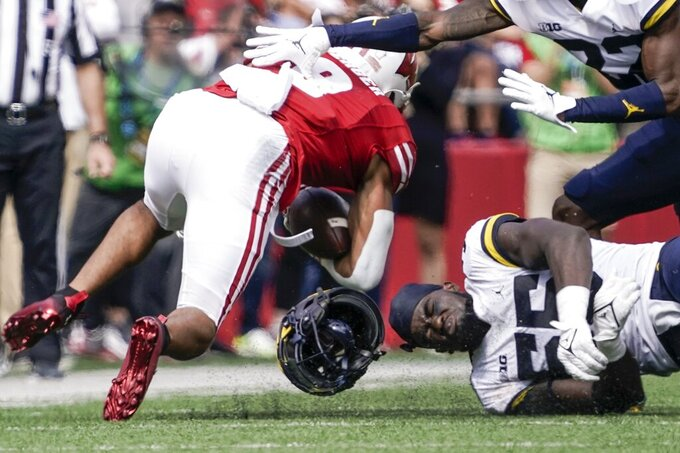 Michigan's David Ojabo loses his helmet as he stops Wisconsin's Jalen Berger during the second half of an NCAA college football game Saturday, Oct. 2, 2021, in Madison, Wis. (AP Photo/Morry Gash)