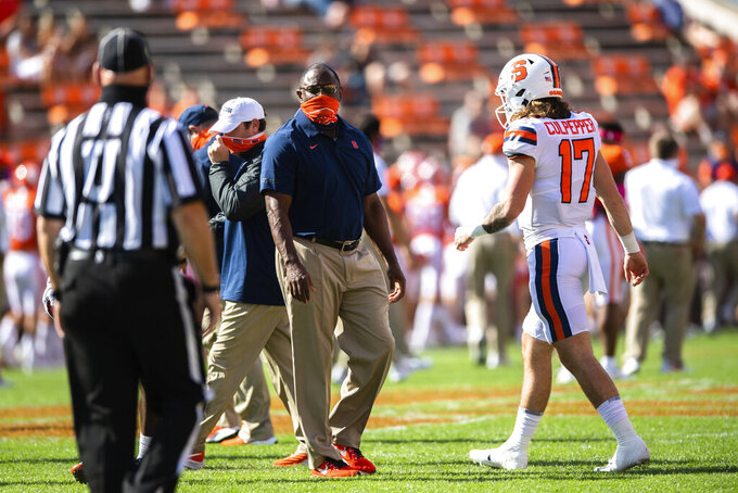 Syracuse head coach Dino Babers, center, and quarterback Rex Culpepper walk on the field before an NCAA College football game against Clemson in Clemson, S.C., on Saturday, Oct. 24, 2020. (Ken Ruinard/Pool Photo via AP)