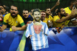 Brazil soccer fans hold a cardboard cutout of Argentina's Lionel Messi after Brazil won 3-1 the final soccer match of the Copa America against Peru at the Maracana stadium in Rio de Janeiro, Brazil, Sunday, July 7, 2019. (AP Photo/Victor R. Caivano)
