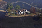 A home between Healdsburg and Windsor, Calif., on Tuesday, Oct. 29, 2019, is surrounded by charred ground but was spared from the Kincade Fire flames. Frustration and anger mounted across Northern California on Tuesday as the state's biggest utility, Pacific Gas & Electric, began another round of widespread blackouts aimed at preventing its electrical equipment from sparking wildfires in high winds. (Guy Wathen/San Francisco Chronicle via AP)