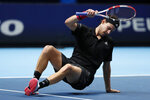 Dominic Thiem of Austria slips over as he plays against Daniil Medvedev of Russia during their singles final tennis match at the ATP World Finals tennis tournament at the O2 arena in London, Sunday, Nov. 22, 2020. (AP Photo/Frank Augstein)