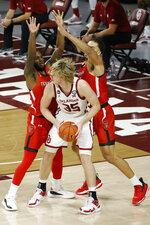 Oklahoma's Brady Malek (35) is guarded by Texas Tech's Jamarius Burton and Marcus Santos-Silva during the second half of an NCAA college basketball game in Norman, Okla., Tuesday, Dec. 22, 2020. (AP Photo/Garett Fisbeck)
