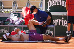 A physiotherapist takes care of Stefanos Tsitsipas of Greece as he plays Serbia's Novak Djokovic during their final match of the French Open tennis tournament at the Roland Garros stadium Sunday, June 13, 2021 in Paris. (AP Photo/Michel Euler)