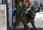 Israeli soldiers throw sound bombs as they clash with Palestinians during a search for suspects of a shooting attack yesterday in the West Bank City of Ramallah, Monday, Dec. 10, 2018. Israeli officials say seven people have been wounded, one critically, in a shooting by a suspected Palestinian assailant outside a Jewish settlement of Ofra in the West Bank. (AP Photo/Majdi Mohammed)