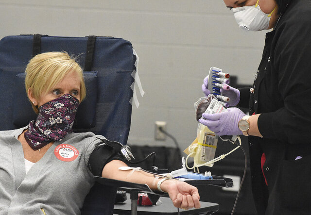 Wearing a homemade mask, Kathy Verhoff of Kalida, Ohio donates blood as phlebotomist Jacqueline Line looks on at the American Red Cross, Tuesday, April 7, 2020 in Lima, Ohio. Approximately 36,000 units of red blood cells are needed every day in the U.S.  (Craig J. Orosz/The Lima News via AP)