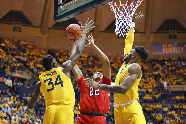 Texas Tech forward TJ Holyfield (22) goes to shoot as he is defended by West Virginia forwards Oscar Tshiebwe (34) and Derek Culver (1) during the first half of an NCAA college basketball game Saturday, Jan. 11, 2020, in Morgantown, W.Va. (AP Photo/Kathleen Batten)