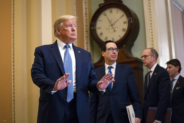 Treasury Secretary Steven Mnuchin listens and President Donald Trump arrives to speak with reporters after meeting with Republican lawmakers on Capitol Hill, Tuesday, March 10, 2020, in Washington. (AP Photo/Evan Vucci)