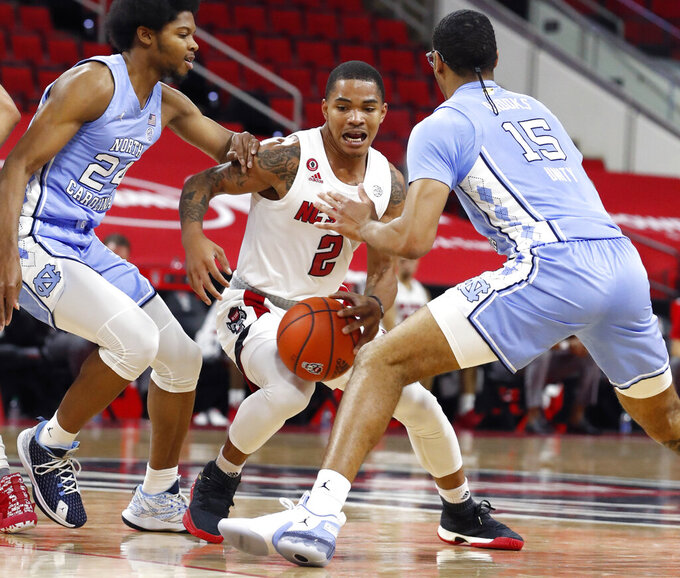 North Carolina State's Shakeel Moore (2) drives between North Carolina's Kerwin Walton, left, and Garrison Brooks during the first half of an NCAA college basketball game in Raleigh, N.C., Tuesday, Dec. 22, 2020 (Ethan Hyman/The News & Observer via AP)