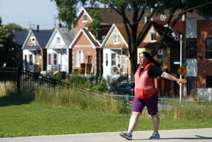 Eugenia Rodriguez walks in Chicago's La Villita Park, Thursday, July 1, 2021. She is required to get out for a walk or a run every morning to keep her varicose veins active and hasn't been eligible for insurance coverage after overstaying a visitor visa from Mexico. Rodriguez used to wake up every two or three hours at night to check on her mother in their Chicago home. Since getting insurance through the Illinois program, her mother has proper medications. (AP Photo/Shafkat Anowar)