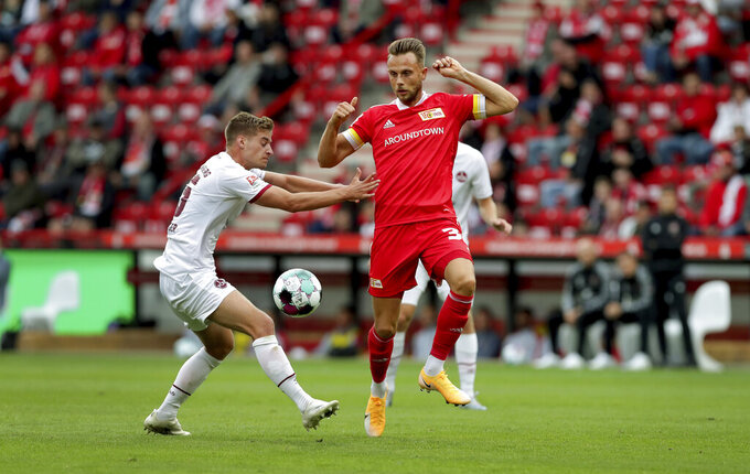 Nuremberg's Johannes Geis, left, and Union's Sebastian Griesbeck, right, challenge for the ball during a friendly soccer match between the German first division, Bundesliga, team 1. FC Union Berlin and the second division team 1. FC Nuremberg in Berlin, Germany, Saturday, Sept. 5, 2020. (AP Photo/Michael Sohn)