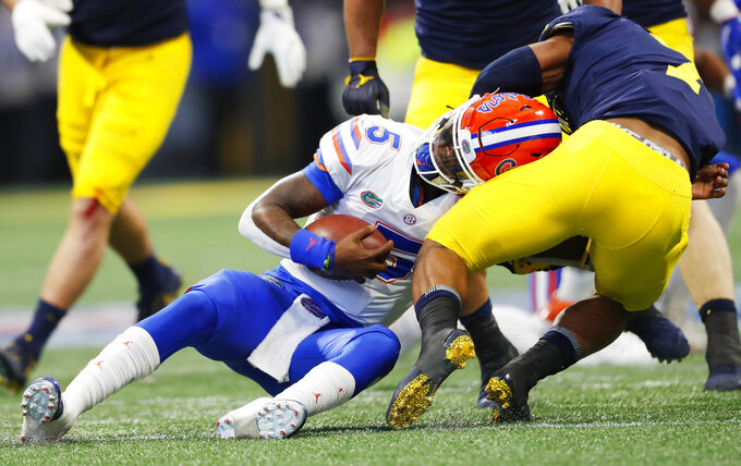 Florida quarterback Emory Jones (5) is hit by Michigan linebacker Khaleke Hudson (7) during the first half of the Peach Bowl NCAA college football game, Saturday, Dec. 29, 2018, in Atlanta. (AP Photo/John Bazemore)