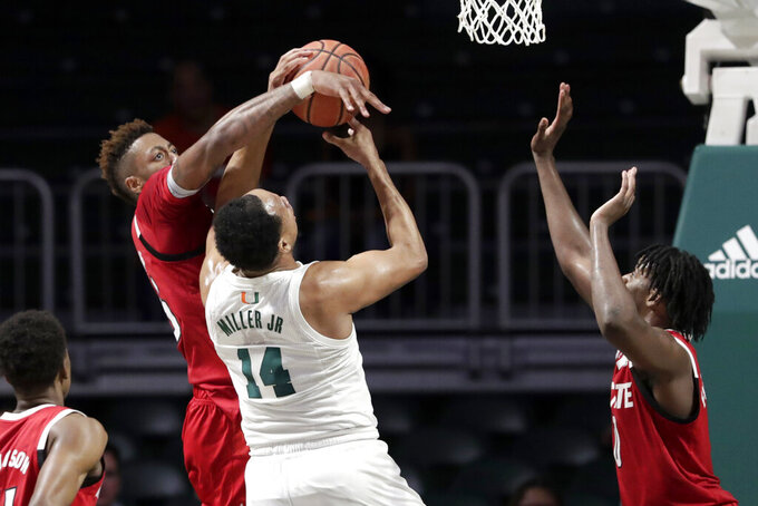 Miami center Rodney Miller Jr. (14) goes to the basket as North Carolina State forward Manny Bates, left, forward DJ Funderburk defend during the first half of an NCAA college basketball game, Wednesday, Feb. 5, 2020, in Coral Gables, Fla. (AP Photo/Lynne Sladky)