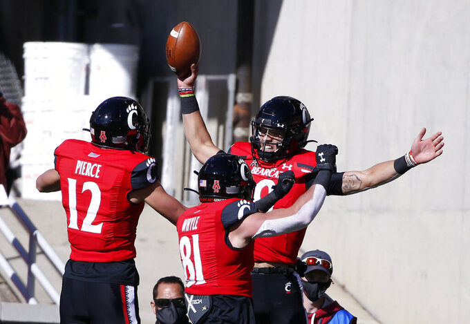 Cincinnati quarterback Desmond Ridder, rear, celebrates a touchdown against Memphis with teammates Alec Pierce (12) and Cam Jones (18) during the first half of an NCAA college football game Saturday, Oct. 31, 2020, in Cincinnati. (Photo by Gary Landers)