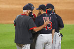 Cleveland Indians pitching coach Carl Willis, left, talks with starting pitcher Aaron Civale during the seventh inning of a baseball game against the Chicago White Sox Friday, Aug. 7, 2020, in Chicago. (AP Photo/Charles Rex Arbogast)