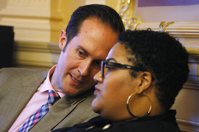 Del. Schuyler VanValkenburg, D-Henrico, left, talks with Del. Marcia 'Cia' Price, D-Newport News, right, during the House session at the Capitol Tuesday, Feb. 25, 2020, in Richmond, Va. Virginia Democrats made nonpartisan redistricting a key campaign plank during last year's off-year election, when they won full control of the statehouse for the first time in a generation. Now in power, they may not pass any reform measures because of internal party divisions. (AP Photo/Steve Helber)