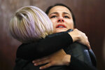 Bailey Kowalski hugs a friend after a news conference in East Lansing, Mich., Thursday, April 11, 2019. The 22-year-old Michigan State University student is speaking publicly a year after suing the school, alleging that three former men's basketball players raped her in 2015 and that she was discouraged by counseling center staff from reporting what happened. (AP Photo/Paul Sancya)