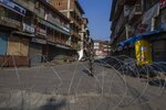 A paramilitary soldier stands guard near a barbwire setup as road blockade at a closed market area in Srinagar, Indian controlled Kashmir, Friday, Sept. 3, 2021. Indian authorities cracked down on public movement and imposed a near-total communications blackout in disputed Kashmir on Thursday after the death of Syed Ali Geelani, a top separatist leader who became the emblem of the region's defiance against New Delhi. (AP Photo/ Dar Yasin)
