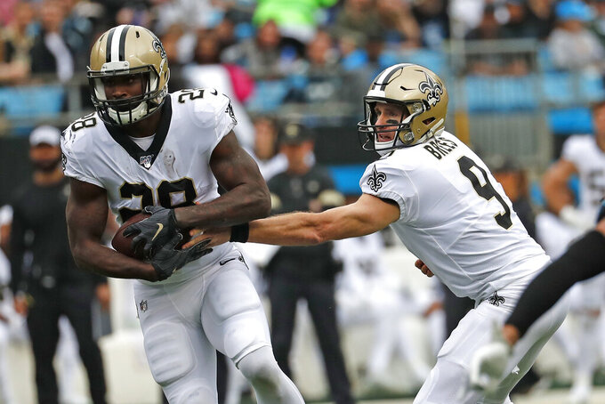 New Orleans Saints quarterback Drew Brees (9) hands off to running back Latavius Murray (28) during the first half of an NFL football game against the Carolina Panthers in Charlotte, N.C., Sunday, Dec. 29, 2019. (AP Photo/Gerry Broome)