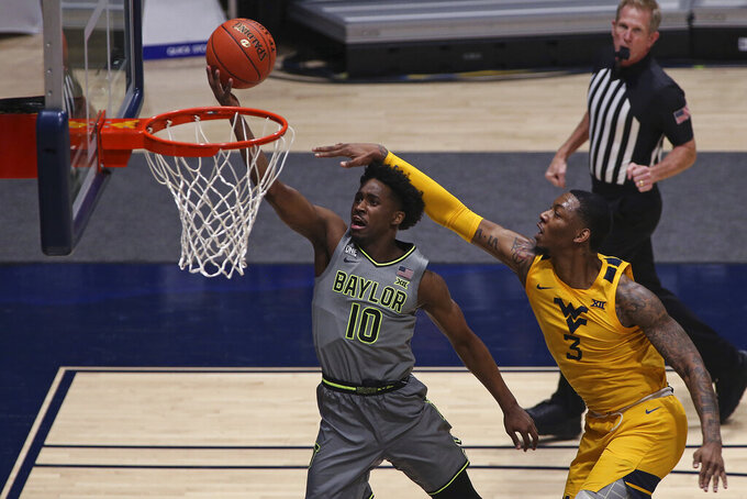 Baylor guard Adam Flagler (10) shoots while defended by West Virginia forward Gabe Osabuohien (3) during the second half of an NCAA college basketball game Tuesday, March 2, 2021, in Morgantown, W.Va. (AP Photo/Kathleen Batten)