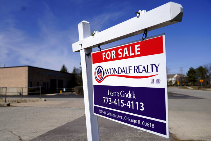 """FILE - In this March 21, 2021 file photo, a """"For Sale"""" sign stands along side a building lot in Wheeling, Ill. Mortgage rates were flat to higher this week, Thursday, June 3. The benchmark 30-year home loan remained below the 3% mark amid continued positive indications of the economy's recovery from the pandemic recession.   (AP Photo/Nam Y. Huh, File)"""