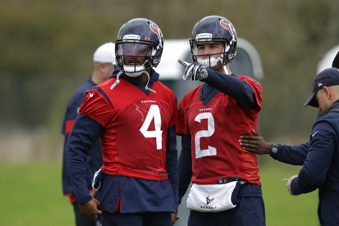 Houston Texans' quarterback Deshaun Watson, 4, talks with quarterback AJ McCarron, 2, during an NFL practice session at the London Irish rugby team training ground in the Sunbury-on-Thames suburb of south west London, Friday, Nov. 1, 2019. The Houston Texans are preparing for an NFL regular season game against the Jacksonville Jaguars in London on Sunday. (AP Photo/Matt Dunham)