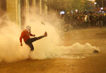 An anti-government protester kicks back a tear gas canister against the riot police, during a protest near the parliament square, in downtown Beirut, Lebanon, Sunday, Dec. 15, 2019. Lebanese security forces fired tear gas, rubber bullets and water cannons Sunday to disperse hundreds of protesters for a second straight day, ending what started as a peaceful rally in defiance of the toughest crackdown on anti-government demonstrations in two months. (AP Photo/Hussein Malla)