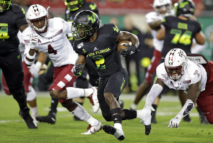 South Florida running back Jordan Cronkrite (2) runs past Temple linebacker Sam Franklin (4) during the first half of an NCAA college football game Thursday, Nov. 7, 2019, in Tampa, Fla. (AP Photo/Chris O'Meara)