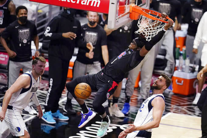 Los Angeles Clippers guard Reggie Jackson dunks between Dallas Mavericks guard Luka Doncic, left, and forward Maxi Kleber during the first half in Game 2 of an NBA basketball first-round playoff series Tuesday, May 25, 2021, in Los Angeles. (AP Photo/Marcio Jose Sanchez)