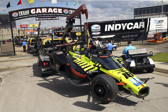 The car of driver Ed Jones is towed to the garage after a multiple-car wreck at the beginning of an IndyCar Series auto race at Texas Motor Speedway on Sunday, May 2, 2021, in Fort Worth, Texas. (AP Photo/Richard W. Rodriguez)