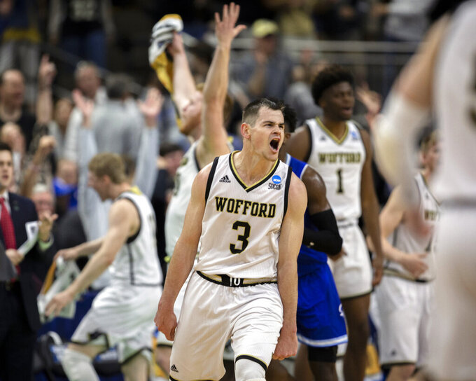 Wofford guard Fletcher Magee (3) celebrates with teammates after hitting a 3-point basket during the final moments of the second half against Seton Hall in a first-round game in the NCAA men's college basketball tournament in Jacksonville, Fla. Thursday, March 21, 2019. (AP Photo/Stephen B. Morton)