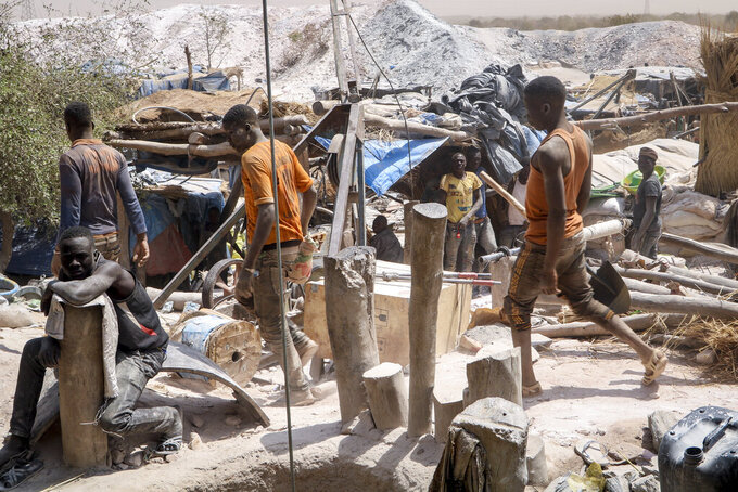 In this photo taken Sunday, Feb. 23, 2020, miners work at a gold mine in Bouda, Burkina Faso. A growing number of small-scale gold miners are out of work in Burkina Faso as jihadists try to seize control of the country's most lucrative industry. (AP Photo/Sam Mednick)