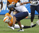 West Virginia's Marcus Simms (8) pulls away from the tackle of Tennessee's Bryce Thompson (20) in the second half of an NCAA college football game in Charlotte, N.C., Saturday, Sept. 1, 2018. (AP Photo/Chuck Burton)