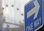 The EU flag hangs from Europa House behind a signpost in London, Tuesday, Sept. 29, 2020. Britain has entered a crucial week of post-Brexit talks with the European Union by rejectingthe EU's demand that it drop plans to breach the legally binding agreementit signed on its departure from the bloc. The EU told British Prime Minister Boris Johnson to brace for a legal fight. (AP Photo/Frank Augstein)