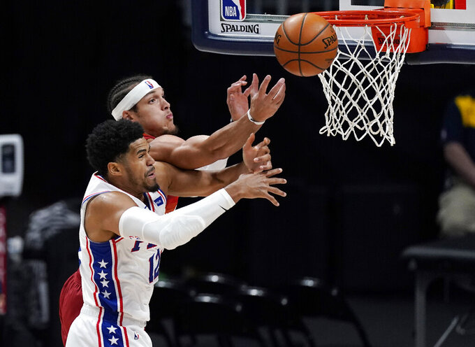 Philadelphia 76ers forward Tobias Harris, front, and Denver Nuggets forward Aaron Gordon fight for control of a rebound in the second half of an NBA basketball game Tuesday, March 30, 2021, in Denver. (AP Photo/David Zalubowski)