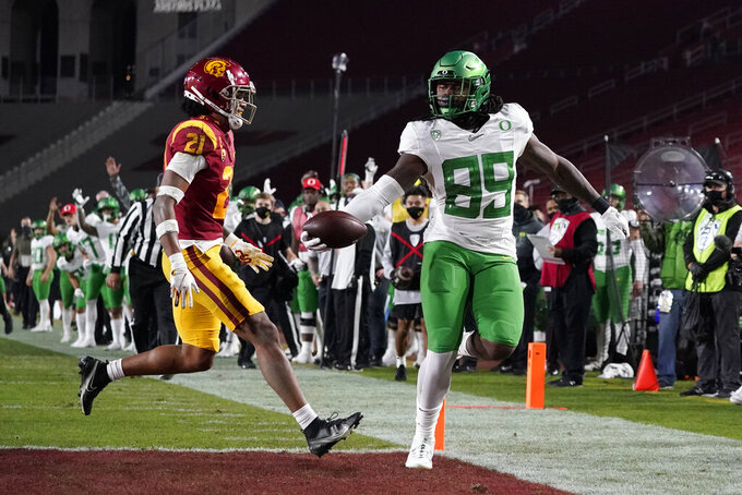 Oregon tight end DJ Johnson (89) runs to the end zone for a touchdown against Southern California safety Isaiah Pola-Mao (21) during the first quarter of an NCAA college football game for the Pac-12 Conference championship Friday, Dec 18, 2020, in Los Angeles. (AP Photo/Ashley Landis)