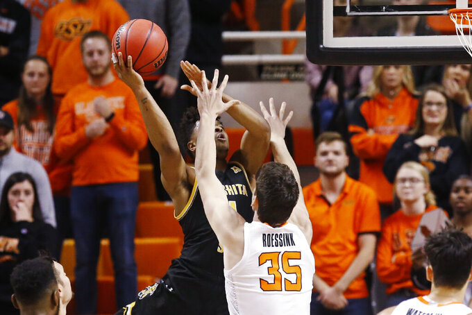 Wichita State guard Tyson Etienne, left, shoots as Oklahoma State forward Hidde Roessink (35) defends in the first half of an NCAA college basketball game in Stillwater, Okla., Sunday, Dec. 8, 2019. (AP Photo/Sue Ogrocki)